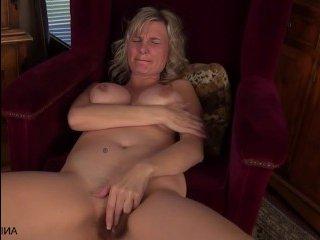 Шикарная небритая мамка мастурбирует свою вагину