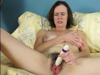 Волосатая мамаша трогает пальцами красную пизду и пихает в нее игрушку
